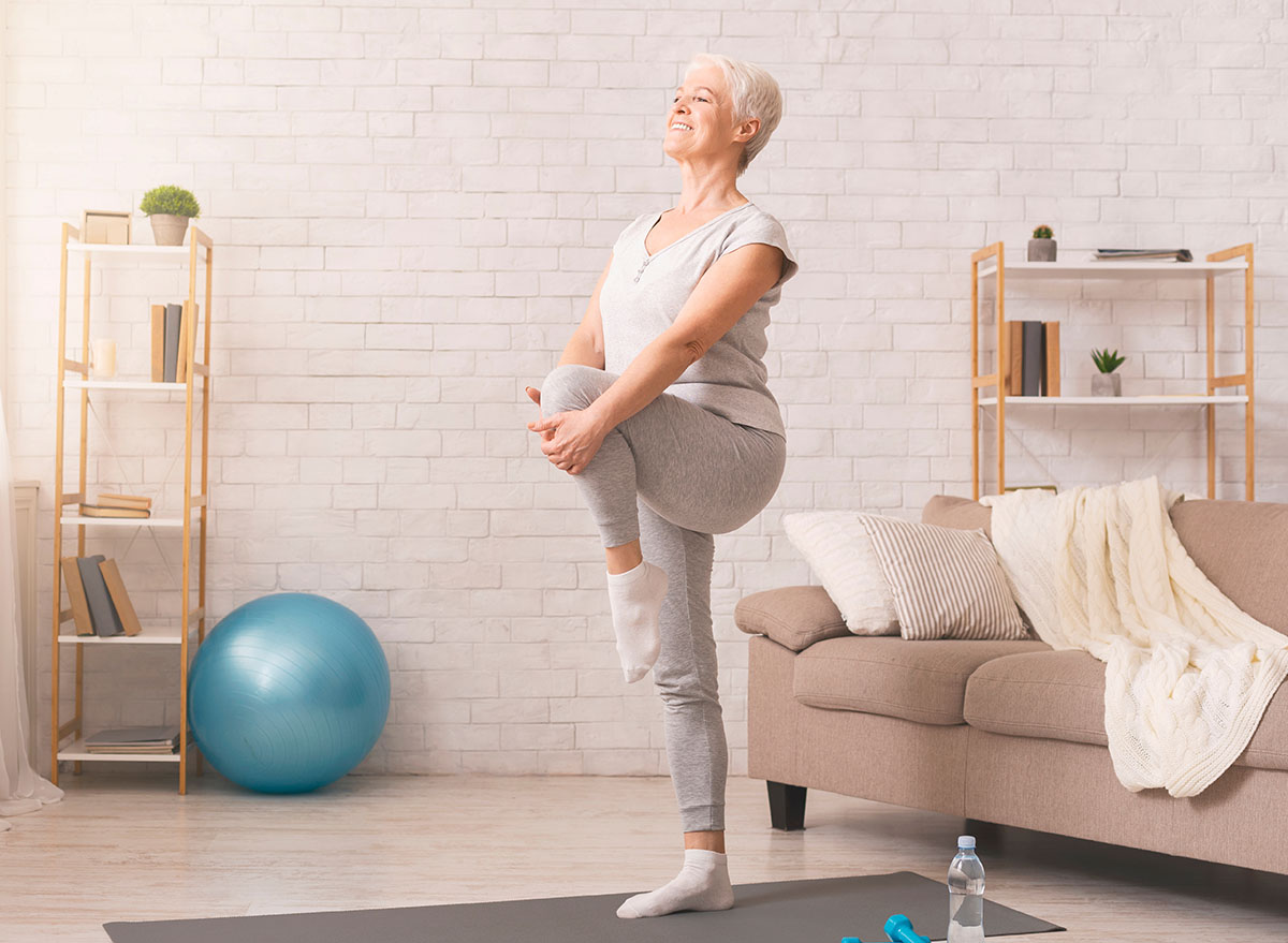 older woman balancing workout in living room