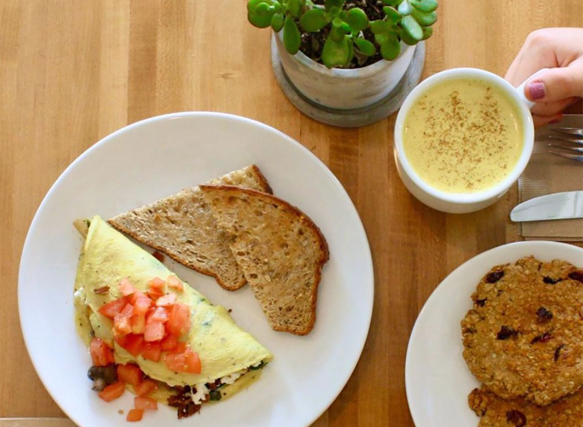 omelet topped with tomatoes and served with toast and coffee