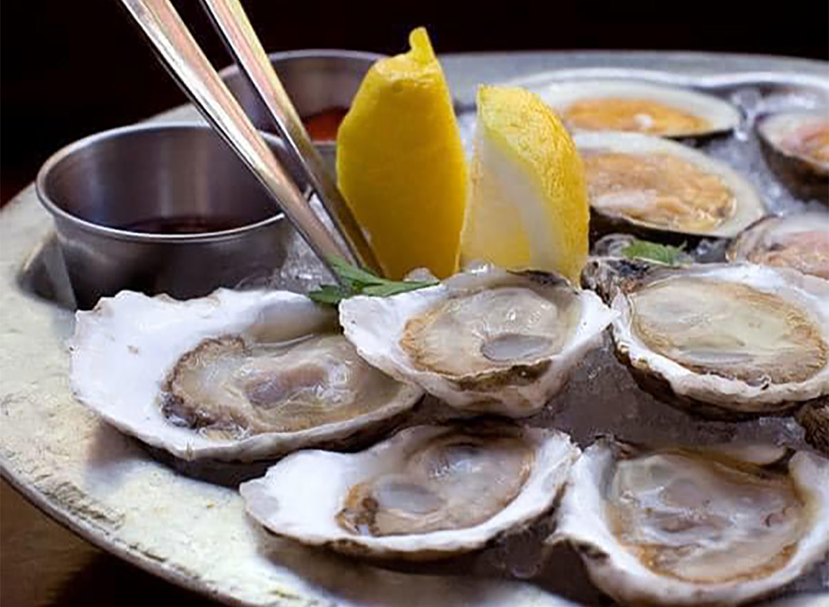 platter of oysters with lemon wedges
