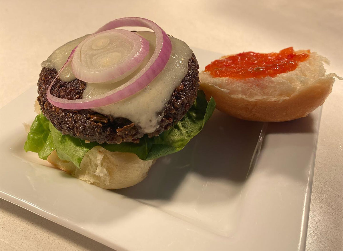 plated veggie burger topped with lettuce and onion