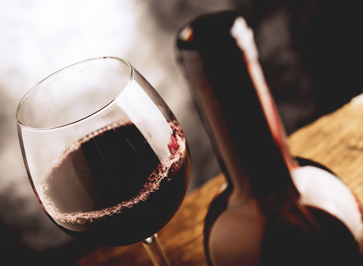 red wine in a glass next to bottle