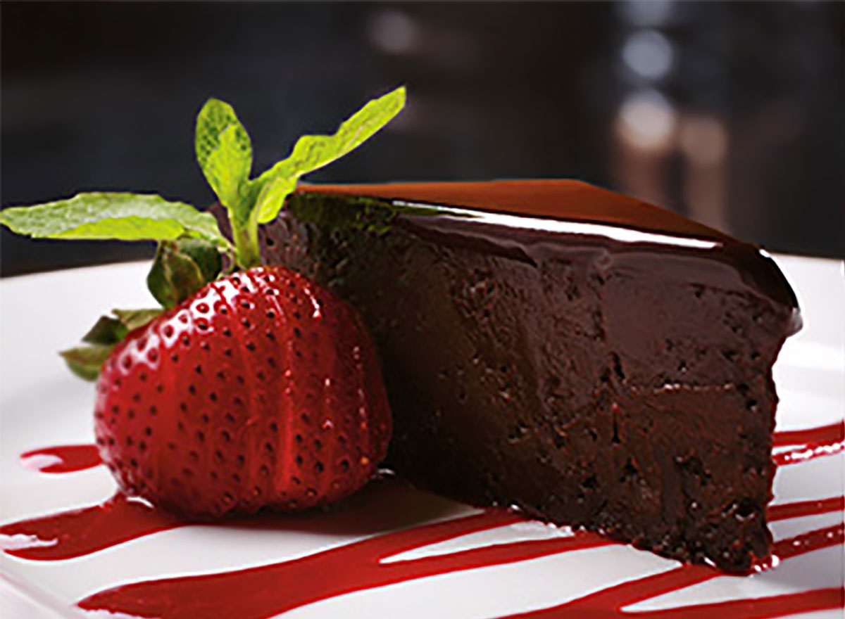 slice of flourless chocolate cake with strawberry syrup drizzle