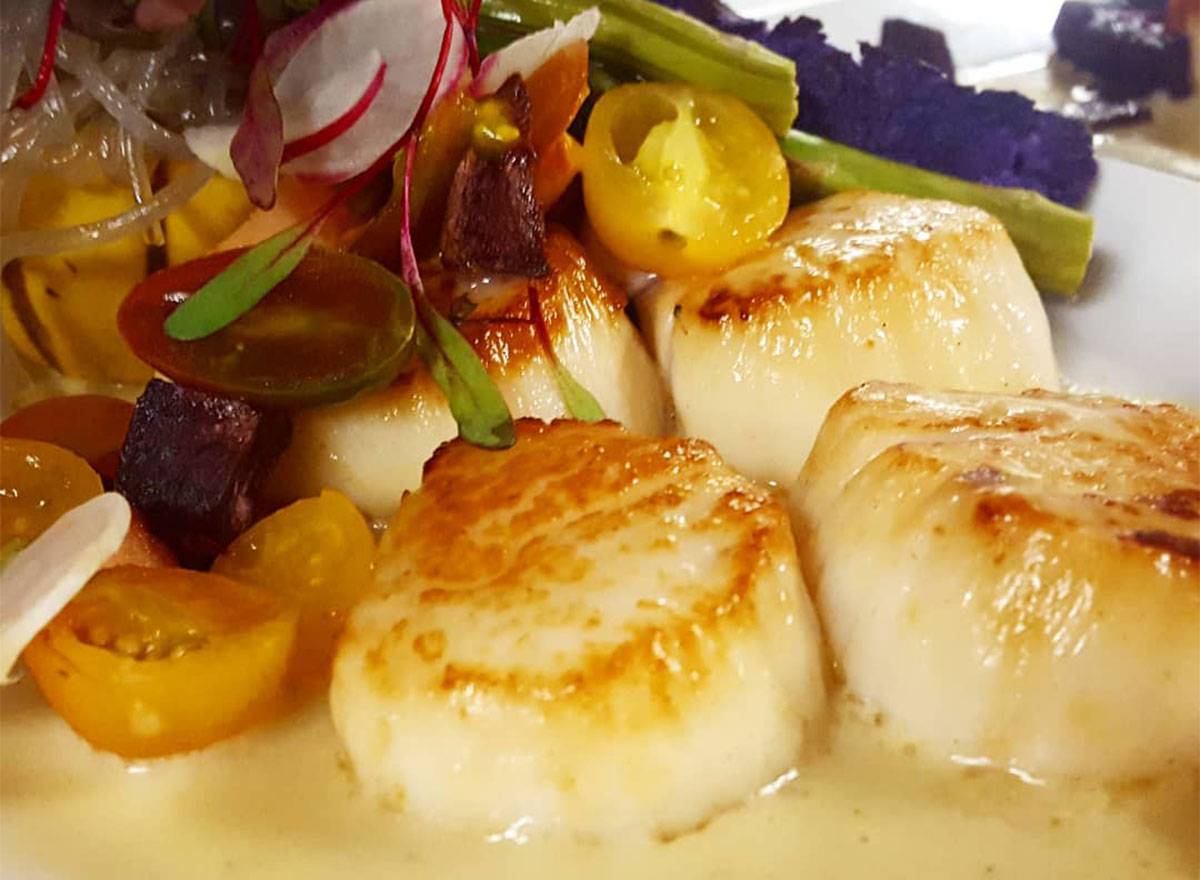 seared scallops with yellow sauce and vegetables