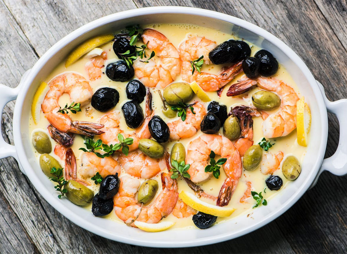 shrimp and olives in oval baking dish with lemon sauce