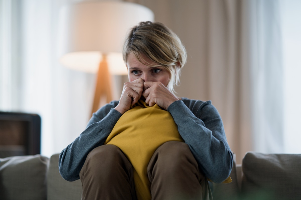 Woman with tablet indoors on sofa at home feeling stressed, mental health concept.