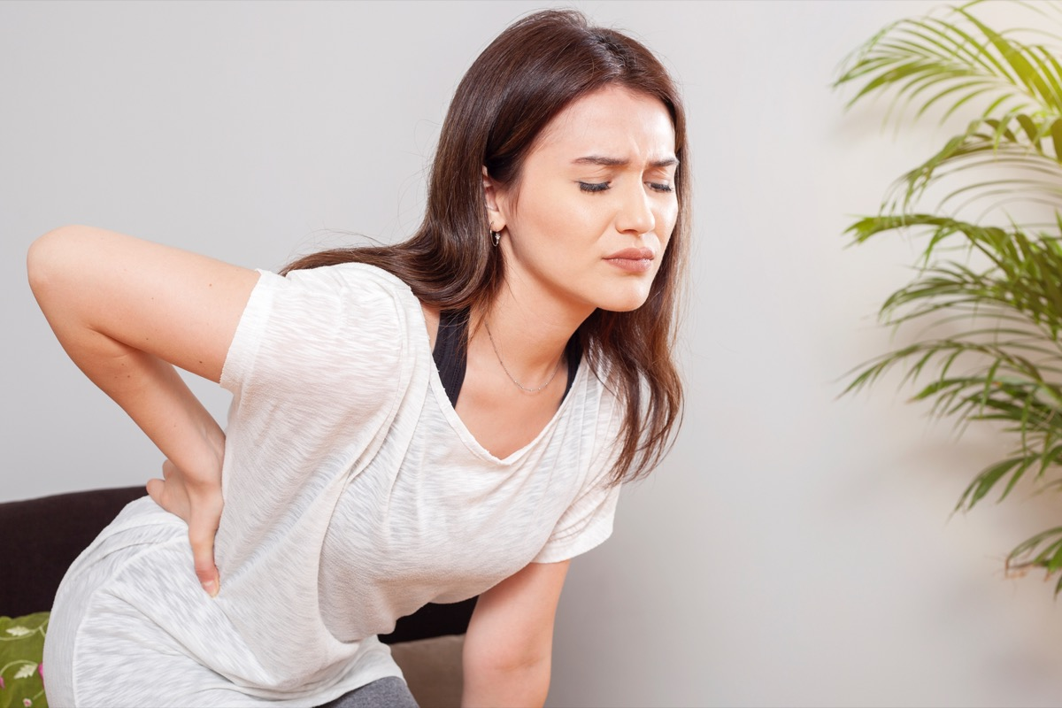 Woman experiencing back ache.