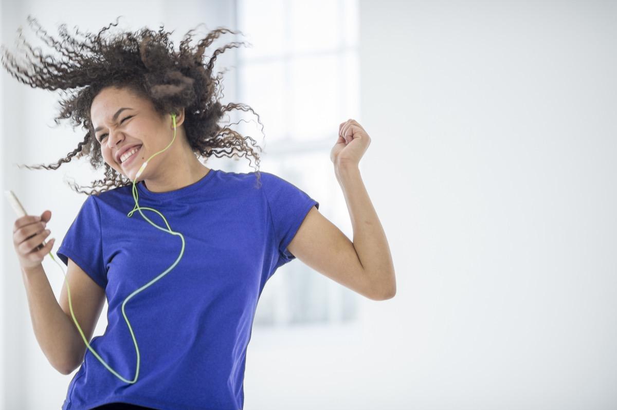 Young woman dancing to music.
