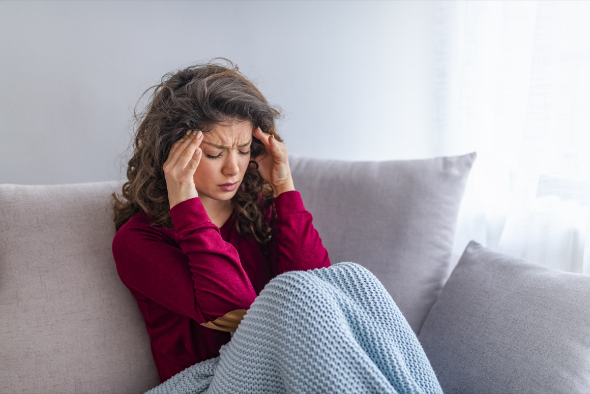 Young woman sitting on a couch, holding her head, having a strong headache. Close up Portrait of young woman with headache.