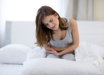 Woman sitting on the bed with pain.