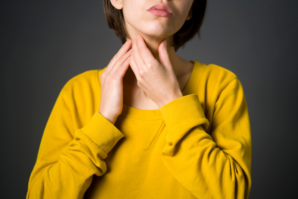 Woman checks the thyroid gland with her hands, keeps her palms on the neck.