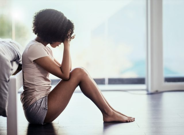 Shot of a young woman suffering from depression in her bedroom