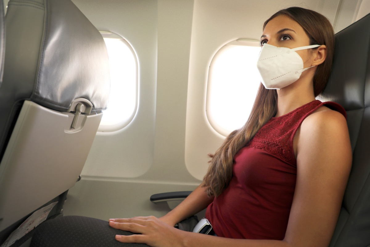 woman sitting inside airplane wearing KN95 FFP2 protective mask