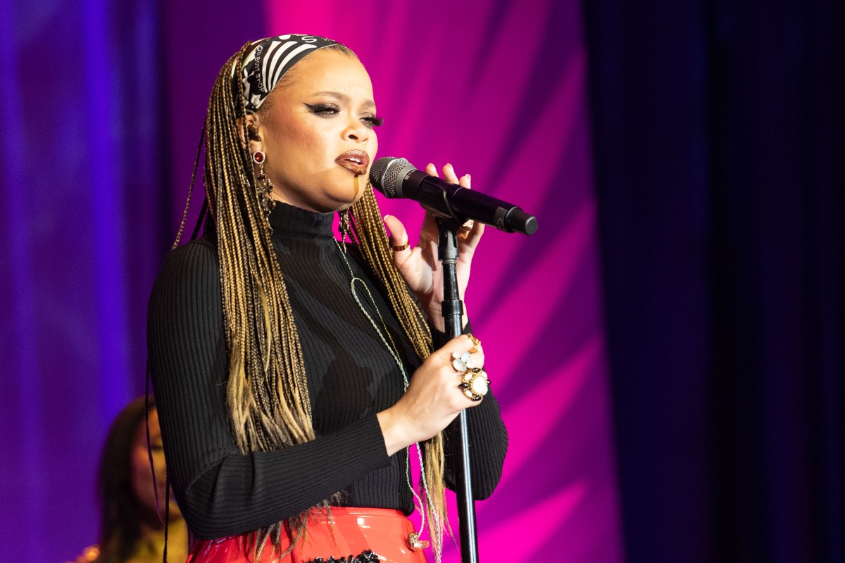 andra day singing into microphone with her hair in blonde cornrow braids