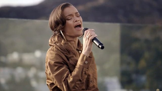 andra day in brown dress singing into microphne
