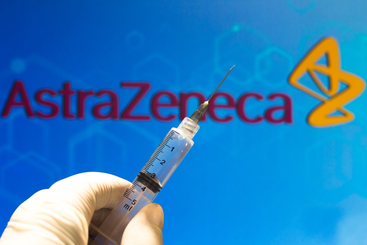 A medical syringe (coronavirus vaccine) is seen with AstraZeneca PLC company logo displayed on a screen in the background.