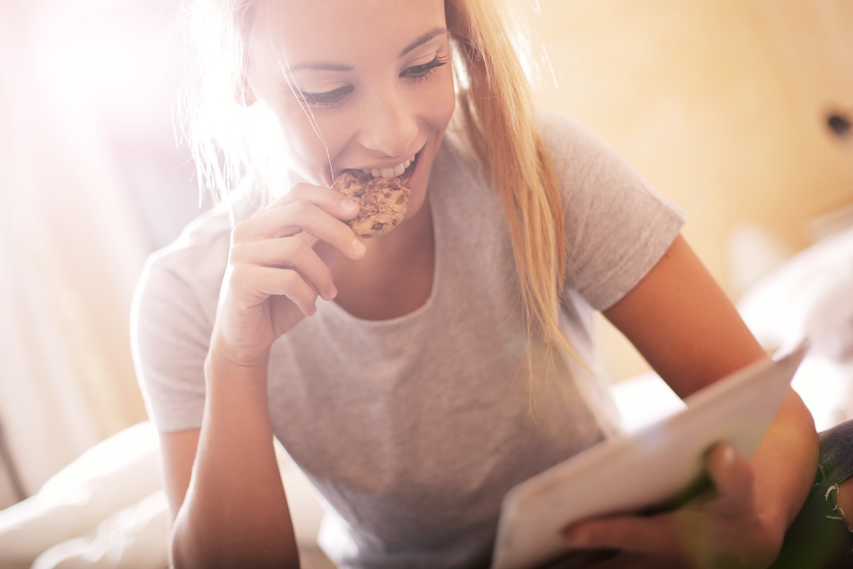 blonde woman eating a cookie and reading