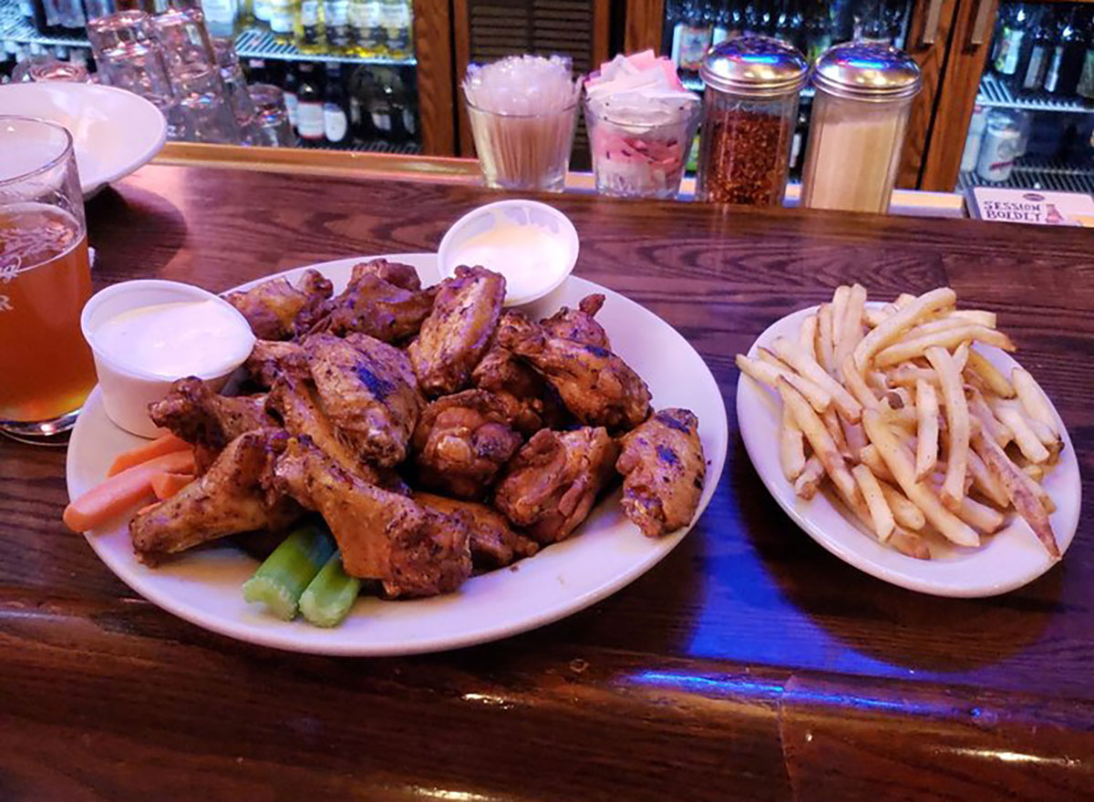 plate of chicken wings with dips and fries