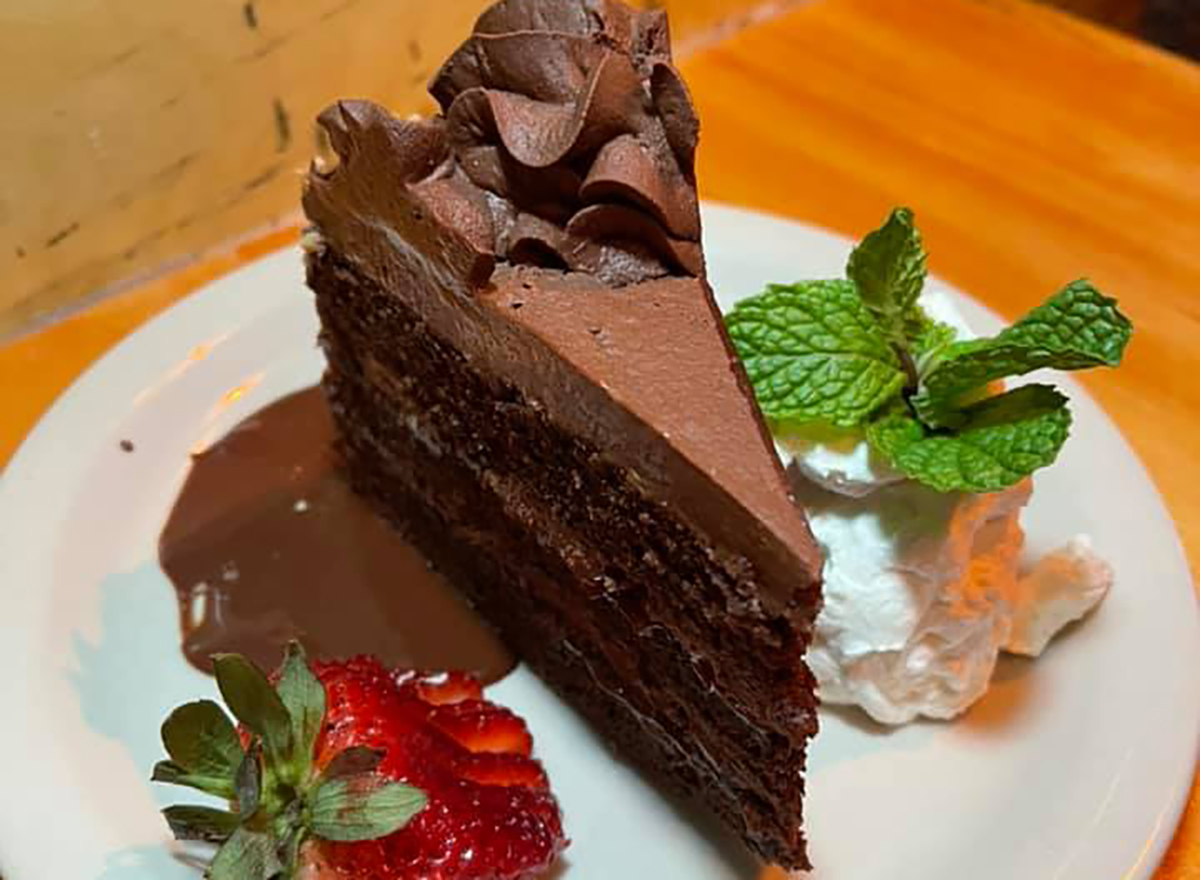 slice of chocolate layered cake with strawberry and whipped cream