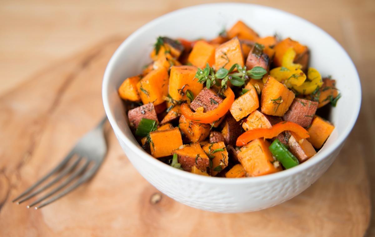 chopped sweet potato in white bowl next to fork