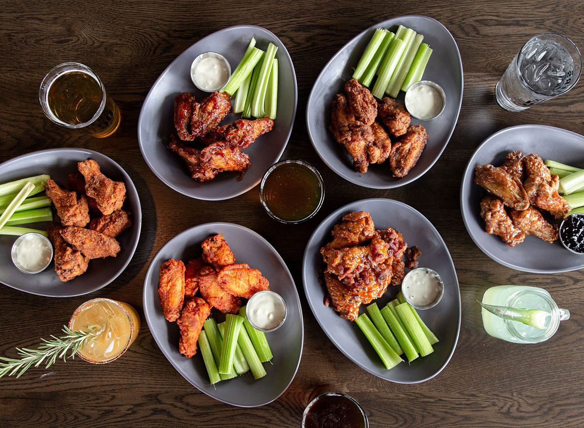 plates of spicy and regular chicken wings with celery slices and bleu cheese dip