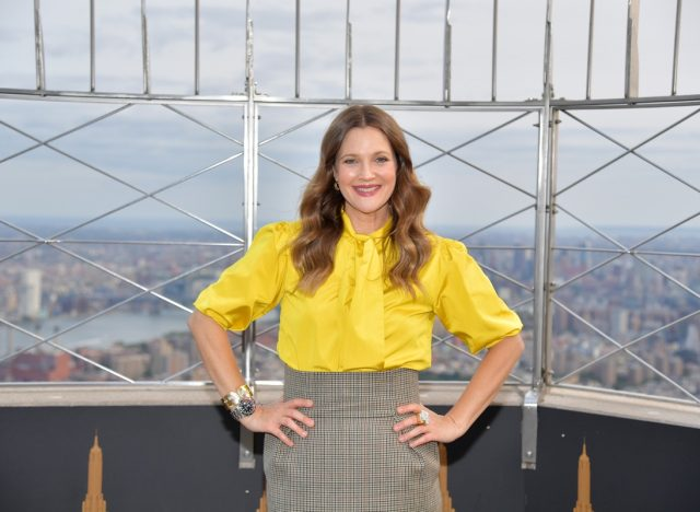 drew barrymore in yellow shirt and gray skirt with hands on her hips