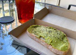 slice of dunkin avocado toast with iced tea