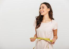 woman smiling measuring waistline