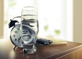 glass of water on nightstand next to alarm clock