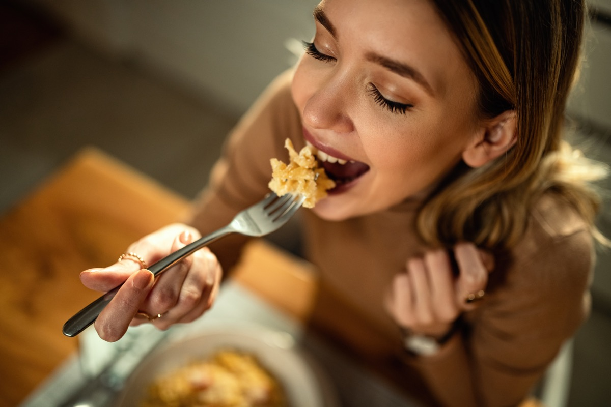 happy woman eating pasta for dinner