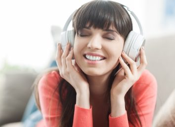 Young smiling woman relaxing and listening to music with headphones