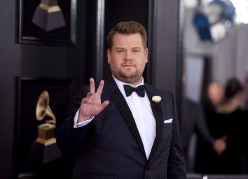 james corden in blue or black suit waving on red carpet