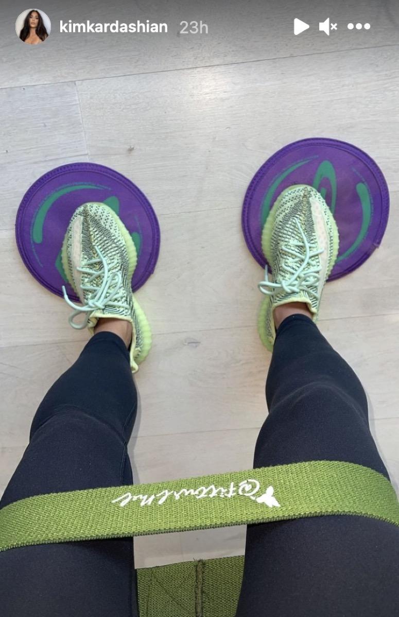 kim kardashian in black leggings standing on purple floor dots in green sneakers