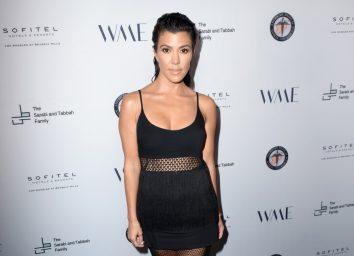 kourtney kardashian in black semi-sheer top and pants on red carpet