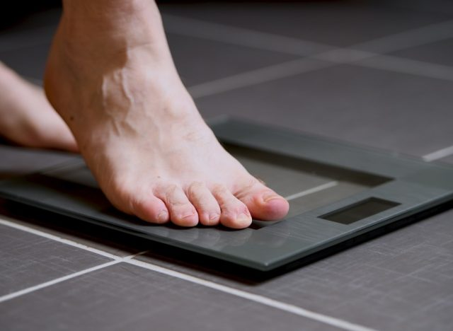 man stepping onto digital scale