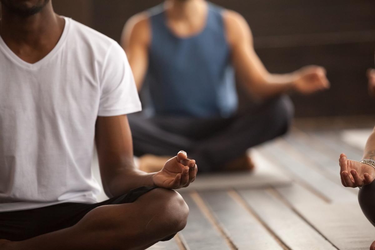 three people in meditation class