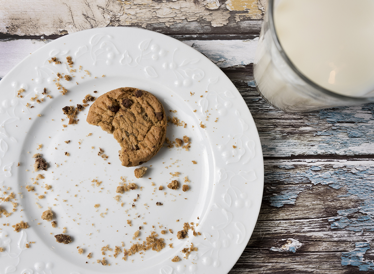 milk and cookies on a plate with crumbs