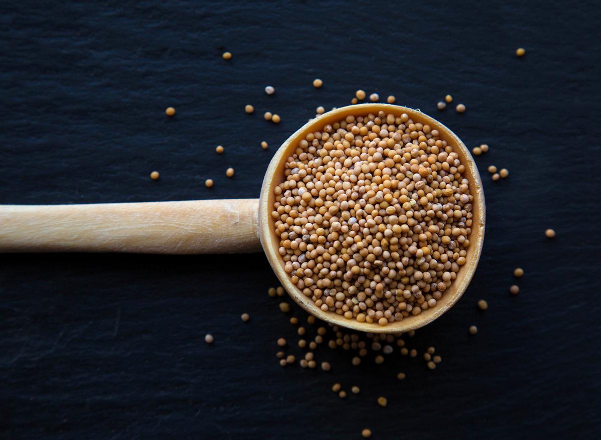 mustard grains in wooden spoon