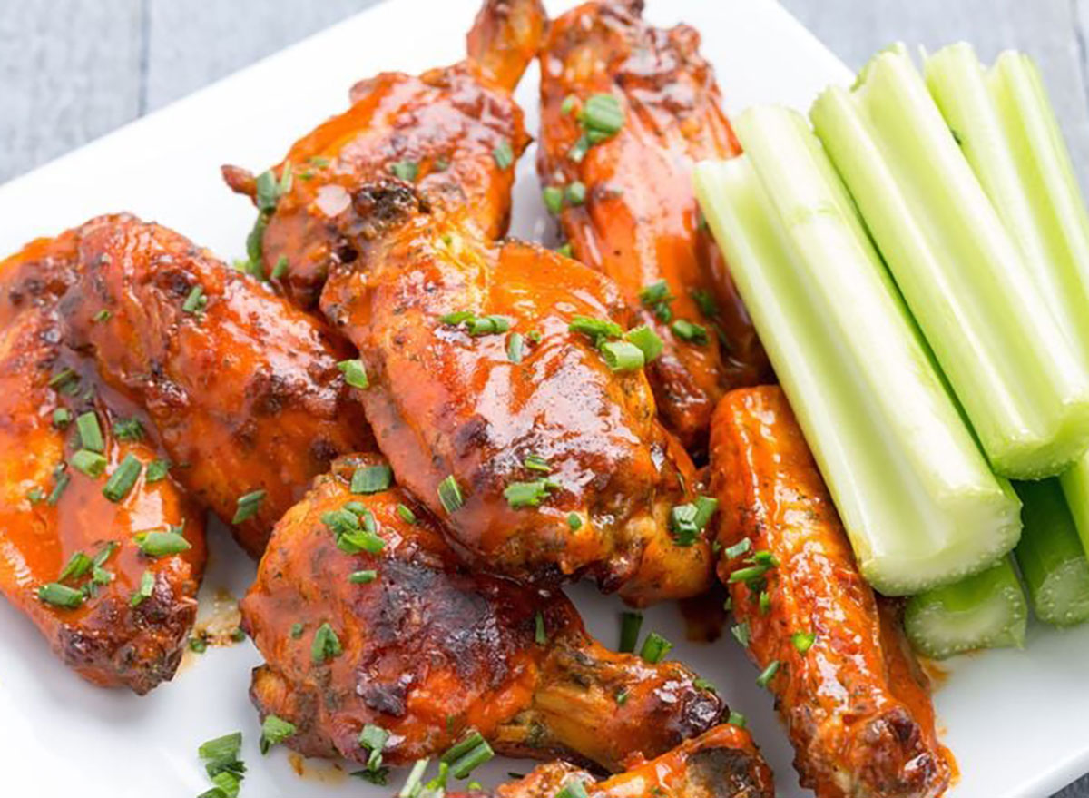 plate of buffalo wings with scallions