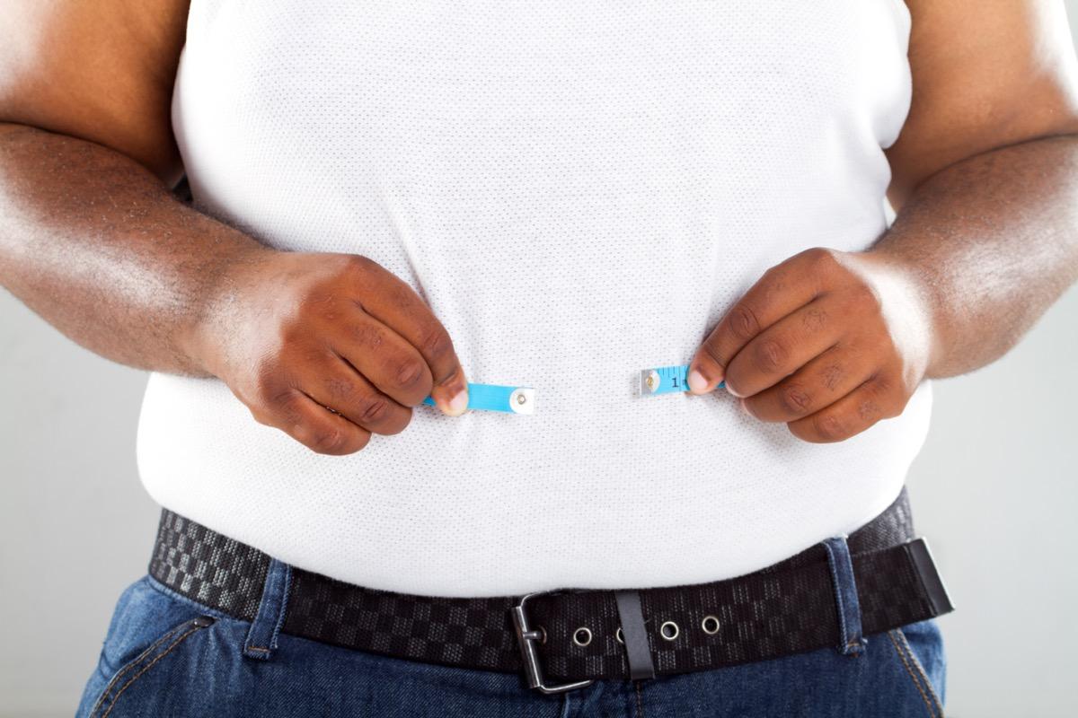 Obese man measuring his waist.