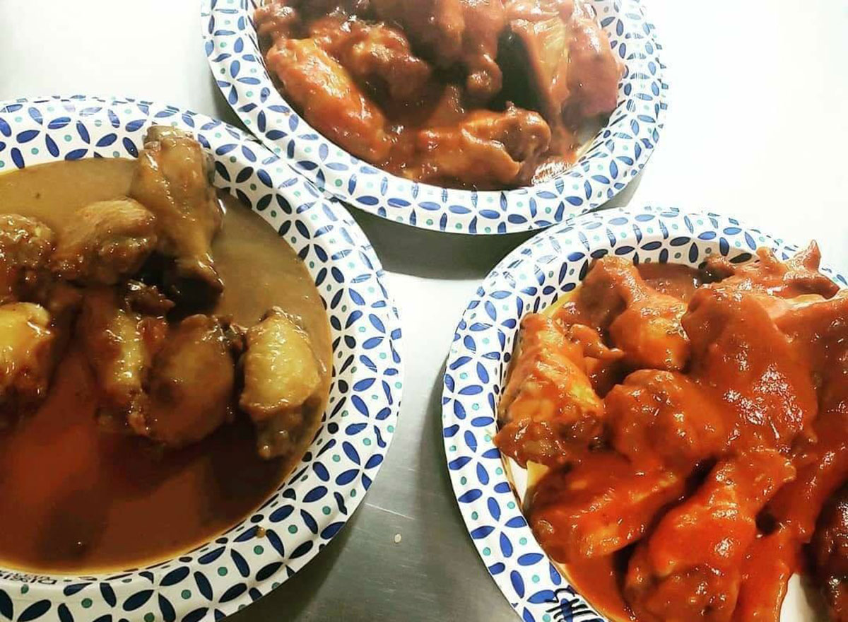 three plates of chicken wings in different sauces
