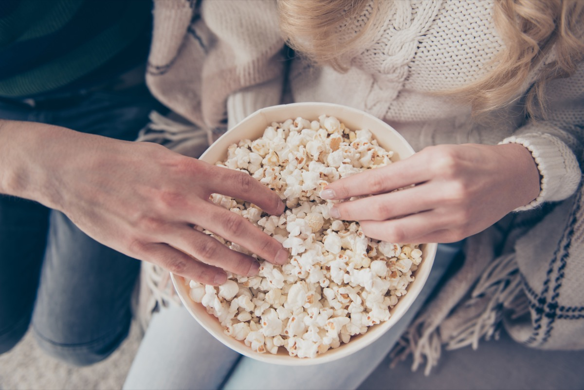 two people in sweaters putting their hands into a bowl of popcorn