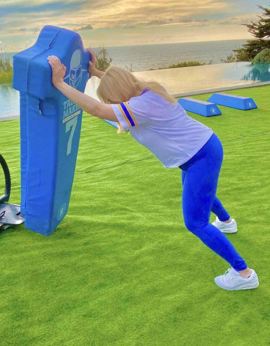 rebel wilson in blue pants and gray t-shirt pushing football barrier