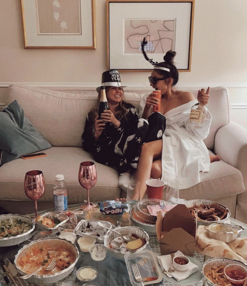 shay mitchell and her friend holding champagne and surrounded by food