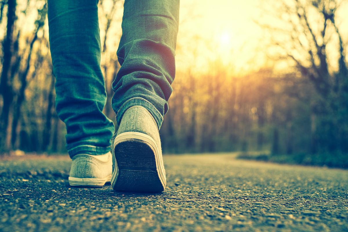 slow walker from behind on a street, wearing jeans
