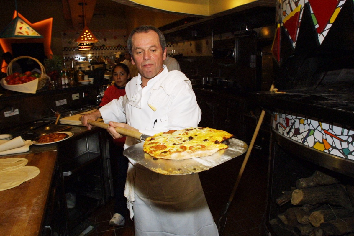 wolfgang puck holding pizza on paddle