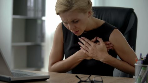 Female manager working on computer, suffering from sharp chest pain.