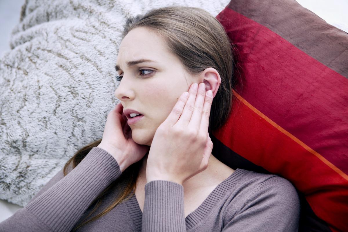 Woman touching her ears.