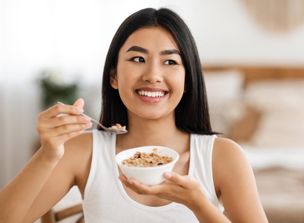 woman eating oatmeal happy
