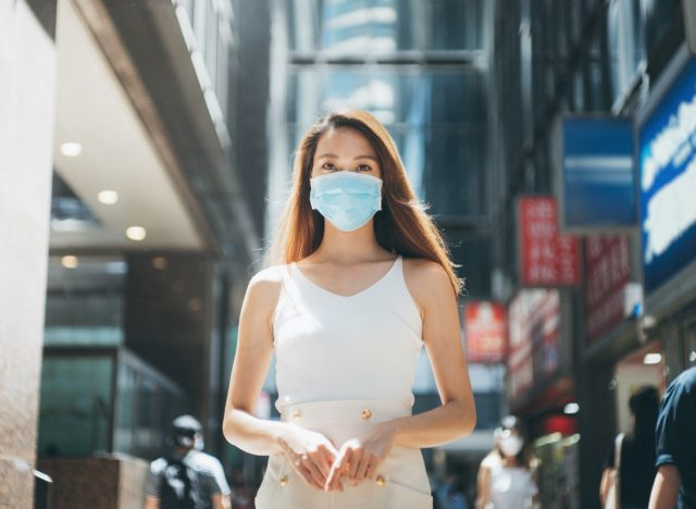 Woman with protective face mask commuting in downtown city street to protect and prevent from the spread of viruses in the city