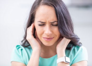 Young woman have headache migraine stress or tinnitus